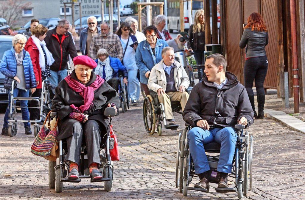 Rollstuhl-Rallye mit Daniel Töpfer: Der Bürgermeister und Gemeinderäte erkunden mit   Rollstuhlfahrern den Ortskern um Barrieren zu finden.   Ingrid Engel zeigt, wo Stolperfallen sind. Foto: factum/Bach