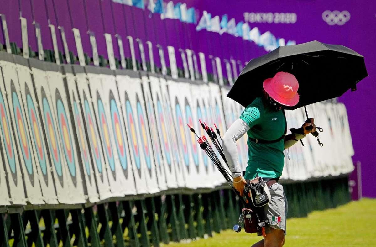 Beim Training schützt sich Bogenschützin Aida Roman aus Mexiko mit einem Schirm gegen die Sonne. Foto: dpa/Charlie Riedel
