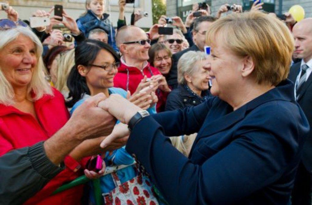 Auch dafür war am Tag der Deutschen Einheit Zeit: Angela Merkel schüttelt in Stuttgart einige Hände. Klicken Sie sich durch die Bilder vom Besuch der Kanzlerin und des Bundespräsidenten Joachim Gauck in Stuttgart! Foto: dpa