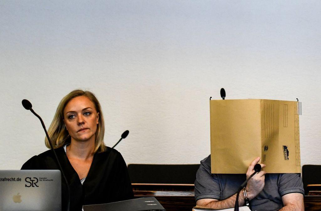 Der wegen Kindesmissbrauchs angeklagte Mann sitzt in Handschellen im Gerichtssaal neben seiner Verteidigerin Mona Hammerschmidt (links) und hält einen Aktendeckel vor sein Gesicht. Foto: dpa