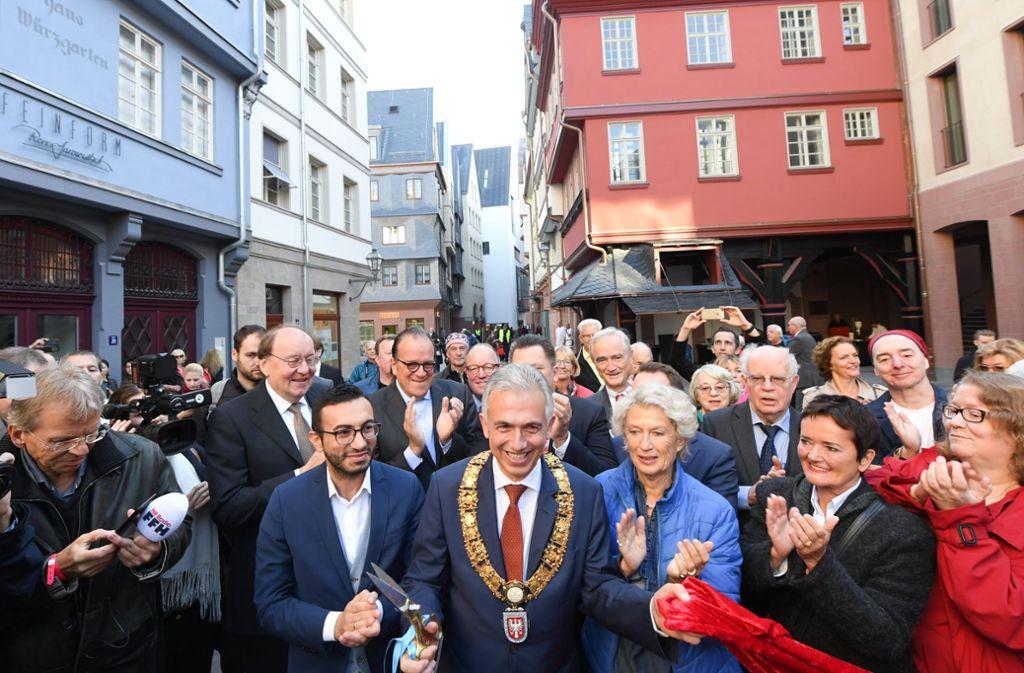 Große Freude: Der Frankfurter Oberbürgermeister Peter Feldmann schneidet das symbolische rote Band zur Eröffnung der Neuen Altstadt durch. Neben ihm seine Vorgängerin Petra Roth und der Planungsdezernent Mike Josef. Foto: dpa
