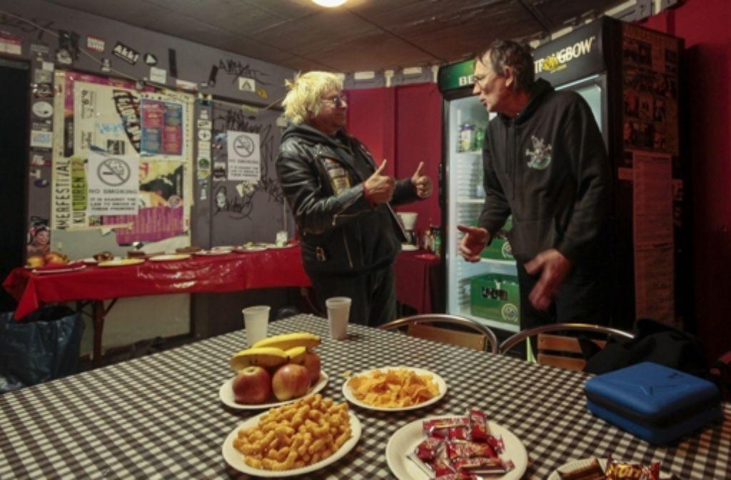 Auf dem Tisch hat Micha Schmidt das Catering drapiert: Flips, Süßwaren und ein wenig Obst. Hier plaudert er mit dem 70 Jahre alten Sänger der UK Subs, Charlie Harper (links). Foto: factum/Granville