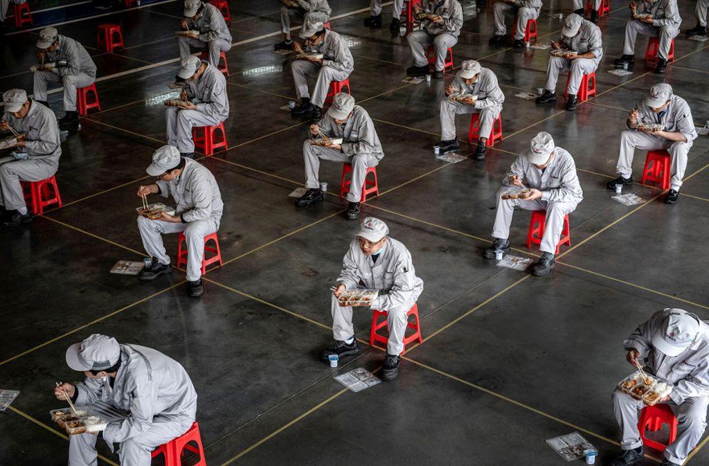 Mitarbeiter einer Autofabrik in Wuhan, China, während ihrer Mittagspause – die Menschen dort dürfen wieder arbeiten gehen, müssen nun aber Abstand zueinander einhalten. Foto: AFP