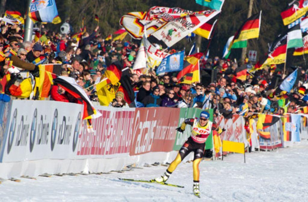 Madgalena Neuner fährt vor den jubelnden Fans zu ihrer ersten Goldmedaille bei der Biathlon-WM in Ruhpolding. Foto: dpa