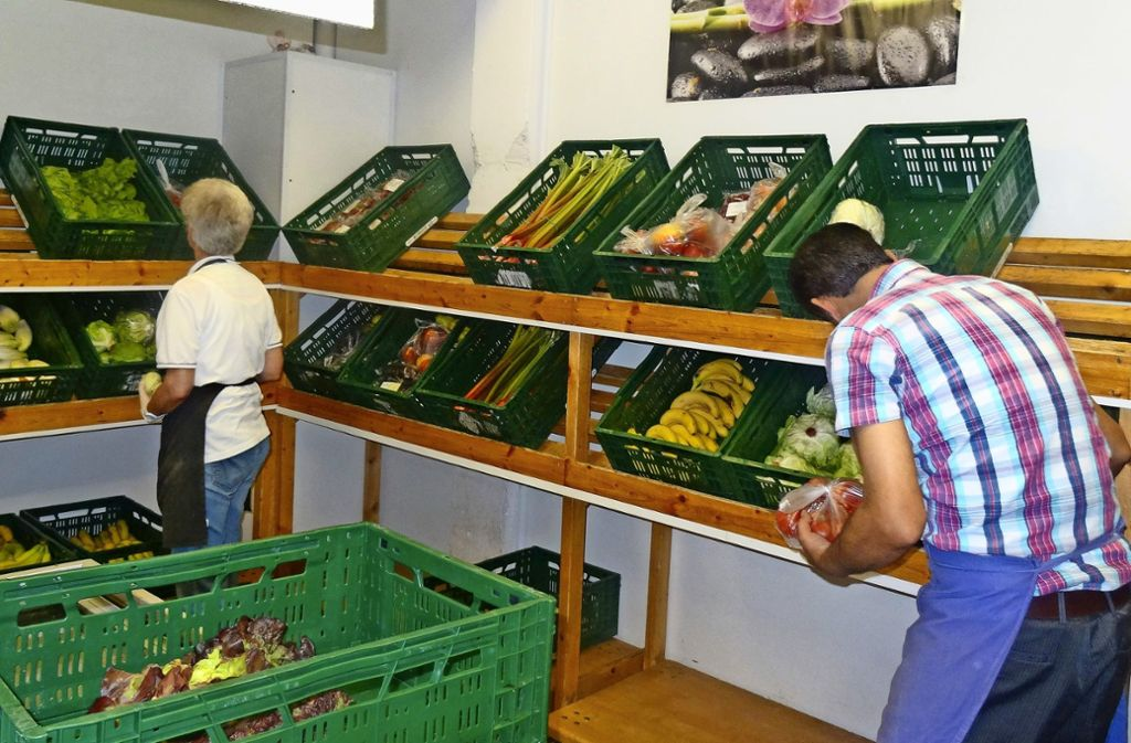 Mitarbeiter der Schwäbischen Tafel Möhringen füllen die Gemüsekisten im Laden auf. Foto: Theresa Ritzer