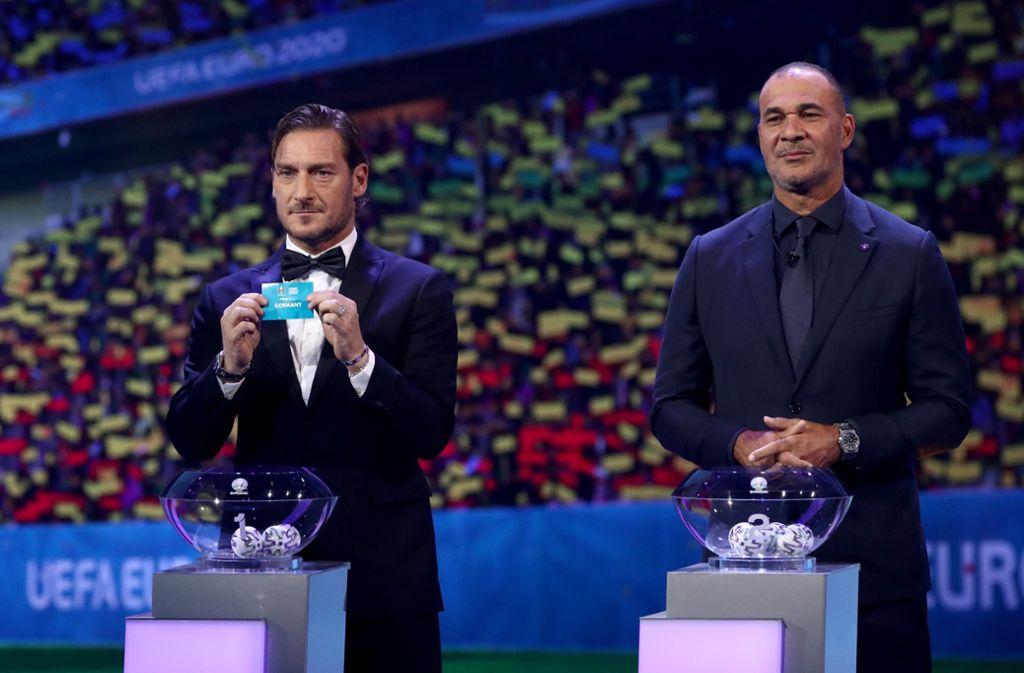Francesco Totti hält das Los für die Deutschland neben Ruud Gullit. Foto: dpa/Christian Charisius