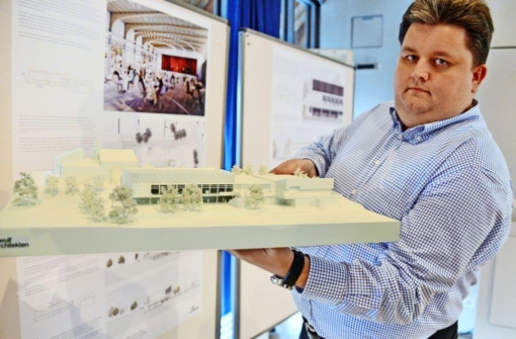 Michael Burkhardt  von der Dorfgemeinschaft (hier mit dem Siegermodell) ist vor allem von der Funktionalität des Siegerentwurfs aus dem renommierten Büro Wulf Architekten überzeugt. Foto: Norbert J. Leven