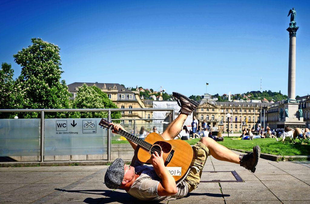 """Rücklings mit zappelnden Beinen liegt Straßenmusiker Kieran Hilbert  bei """"Highway to Hell"""" auf dem Schlossplatz-Boden. Foto: Lichtgut/Achim ZweygarthLichtgut/Achim Zweygarth"""