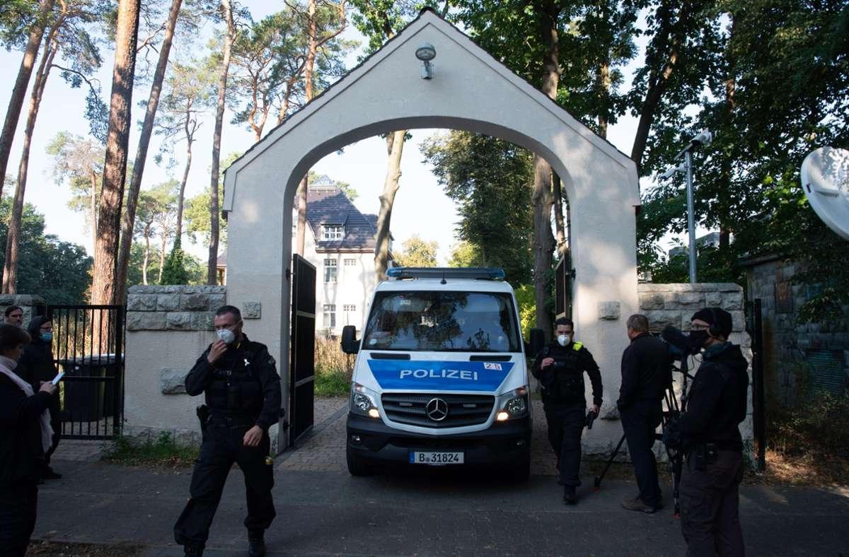 Polizeibeamte stehen im Rahmen einer Durchsuchung vor einem Grundstück in Kleinmachnow. Foto: dpa/Paul Zinken