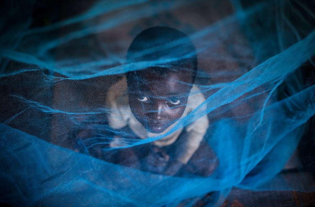 Ein Flüchtlingskind aus Burundi sitzt in Gashora (Ruanda) unter einem Moskitonetz gegen Malaria. Foto: Dai Kurokawa/dpa