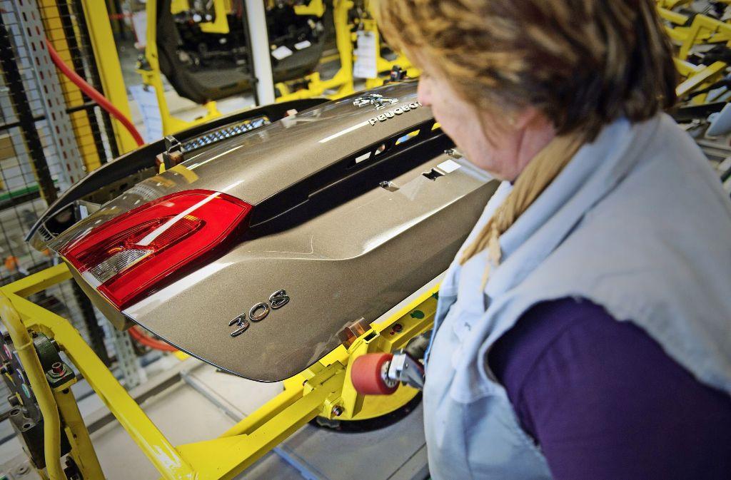 Das Peugeot-Werk im französischen Sochaux (oben) und Opel in Rüsselsheim könnten bald zum gleichen Konzern gehören. Foto: AFP, dpa