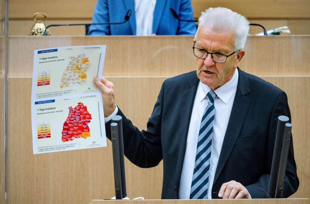 Ministerpräsident Winfried Kretschmann im Landtag mit zwei Karten, die die Entwicklung des Infektionsgeschehens innerhalb von wenigen Wochen dokumentieren. Foto: dpa/Sebastian Gollnow