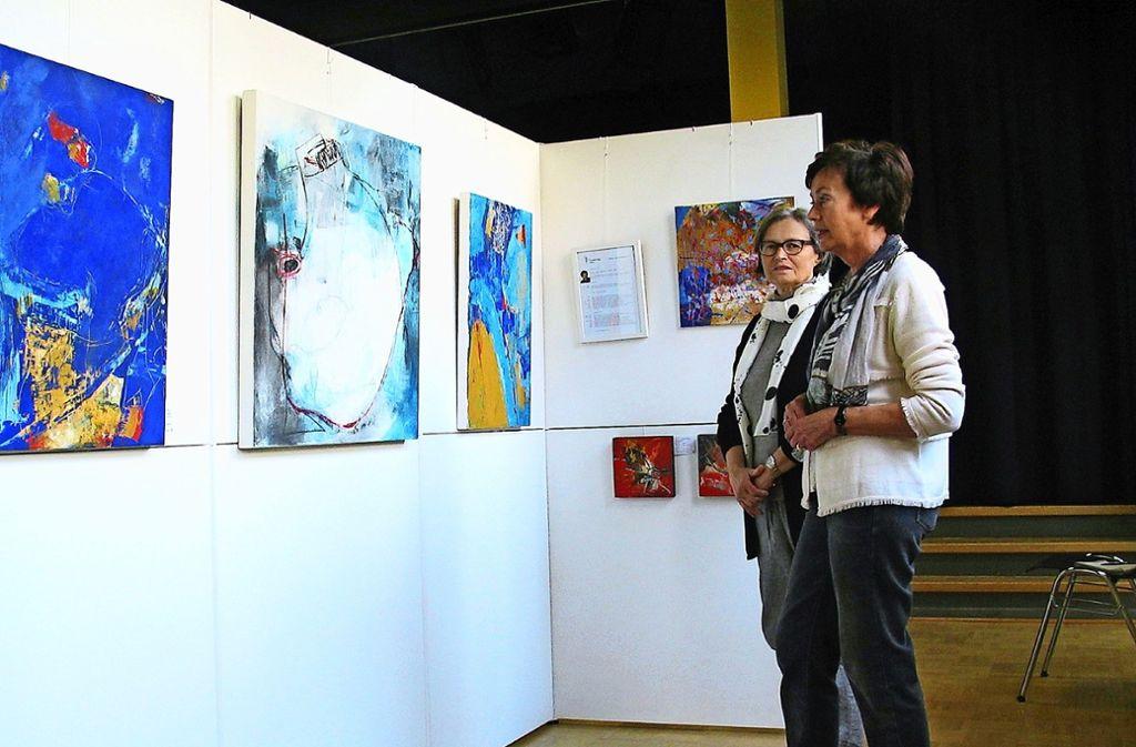 Hermine Neuschwander (rechts) und Inge Hoppmann mit Arbeiten von Ursula Fleig. Die drei Künstlerinnen  gehören zur  Botnanger Malgruppe. Foto: Susanne Müller-Baji