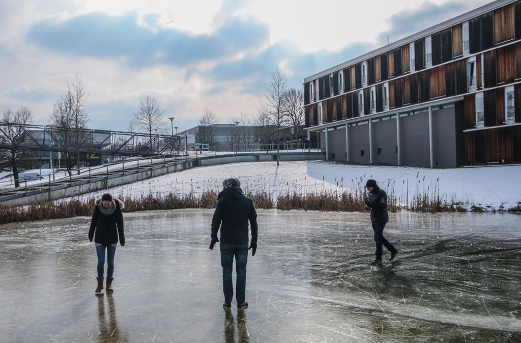 Studenten auf dem Vaihinger Uni-Campus spazieren über einen zugefrorenen Teich. Foto: Yannik Buhl