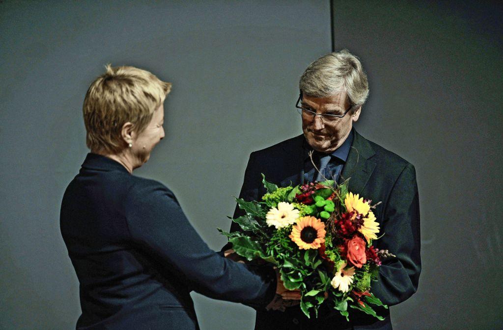 Regionaldirektorin Nicola Schelling beglückwünscht Thomas Bopp mit einem  Blumenstrauß. Foto: Lichtgut/Max Kovalenko