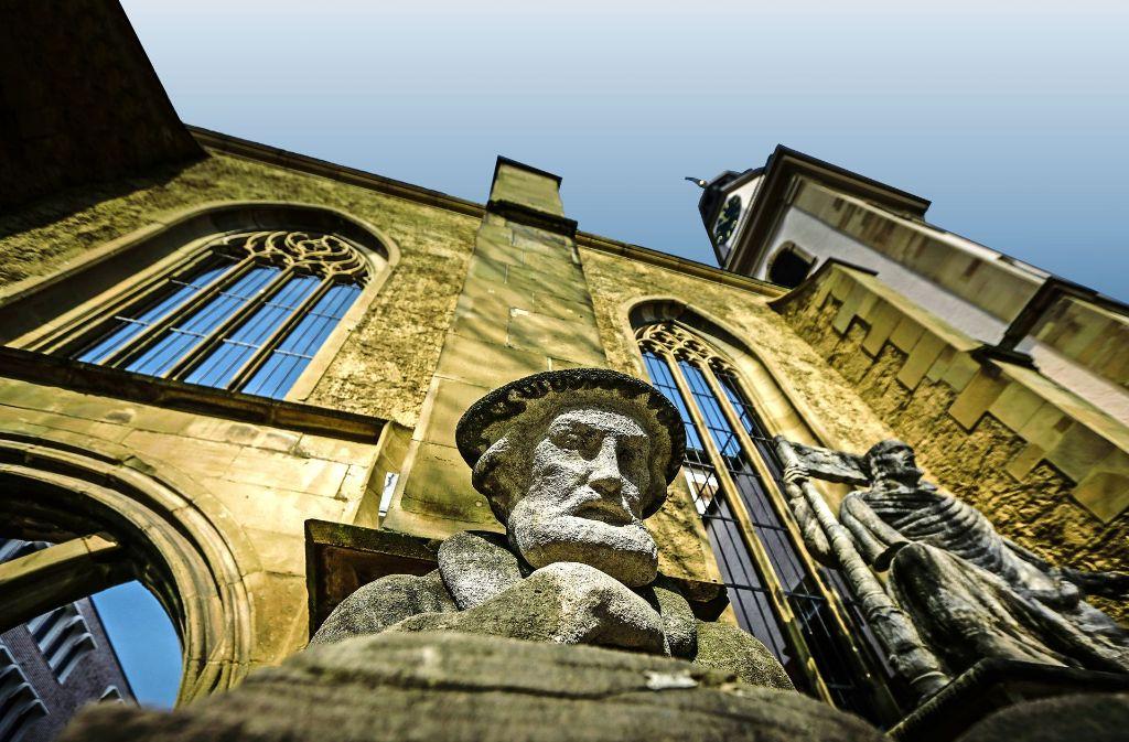 Blick in die Bibel: Die Skulpur von Johannes Brenz vor der Hospitalkirche. Foto: Lichtgut/Leif Piechowski