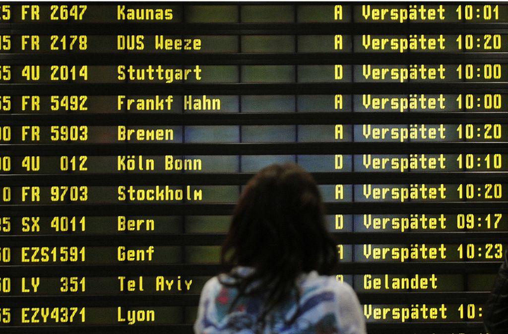 Eine Frau steht auf dem Flughafen Berlin-Schönefeld vor einer Anzeigetafel, auf der verspätete Flüge aufgelistet werden. Foto: Hannibal Hanschke/dpa