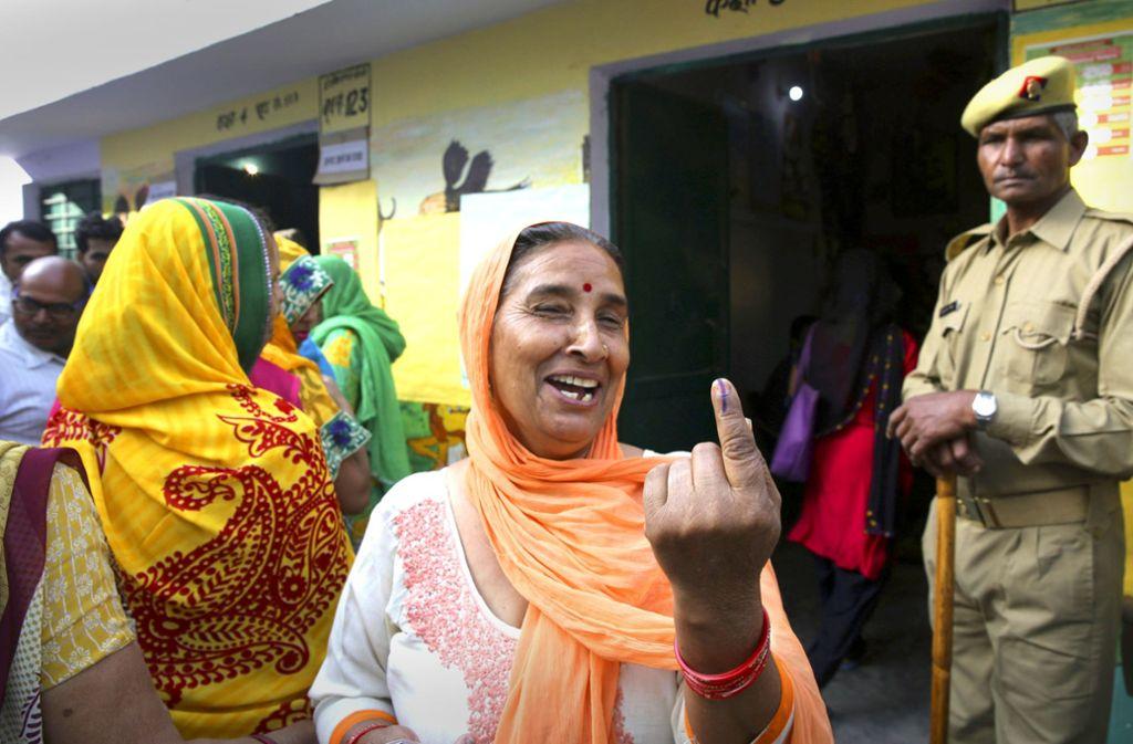 Eine Wählerin zeigt ihren mit Tinte verfärbten Zeigefinger, nachdem sie ihre Stimme an einem Wahllokal abgegeben hat. Foto: AP
