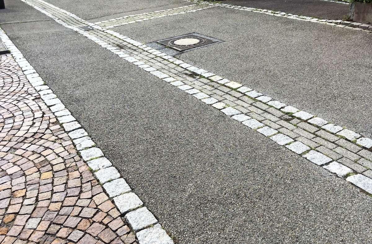 Die geteerte Fahrbahnen wird von Bändern aus helleren Steinen gesäumt. Links im Bild zieht sich ein Gehweg neben der Fahrbahn. Er hebt sich durch ein Band aus einer anderen Steinart von der Straße ab. Ein Parkplatz wiederum zeigt sich mit roten Steinen, die in einem Schuppenmuster aufgebracht wurden. Foto: oh
