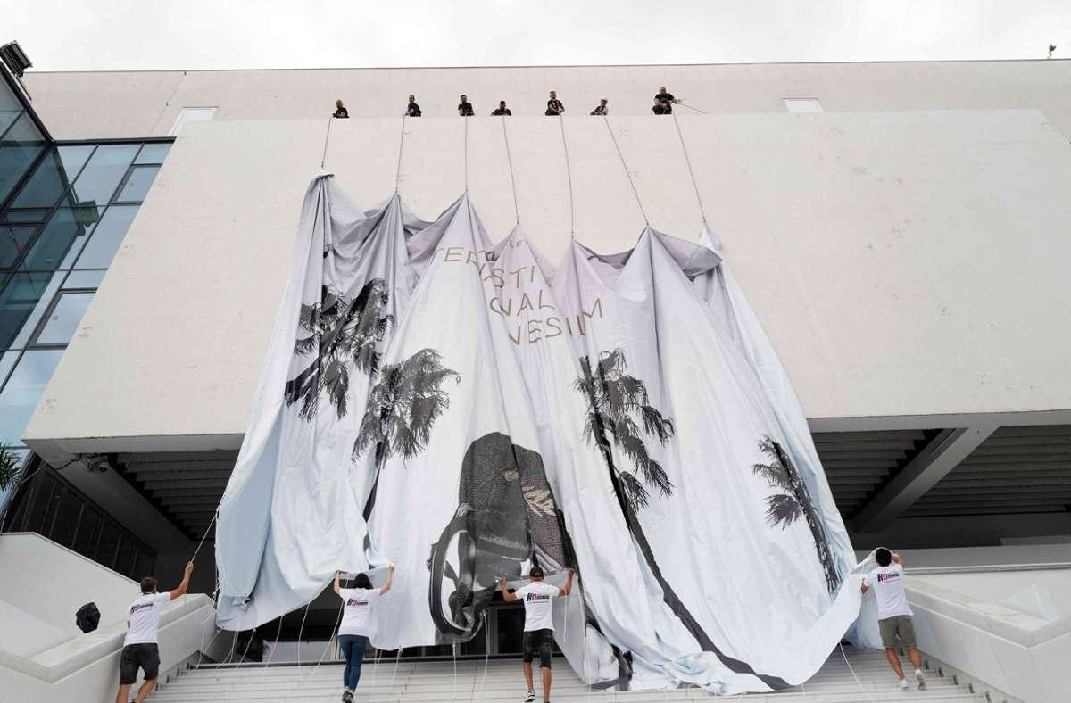 Mitarbeiter bringen ein riesiges Banner  am Festival- und Kongresspalast (Palais des Festivals et des Congres) in Cannes an. Die Filmfestspiele  beginnen am Abend des  6.  Juli. Foto: dpa/Valery Hache