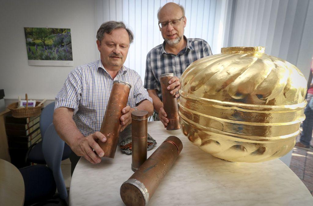 Der Archivar Klaus Herrmann (links) und der Pfarrer Jochen Helsen sind beeindruckt, welche Dokumente in der  Kirchturmkugel aufbewahrt sind. Foto: factum/Granville
