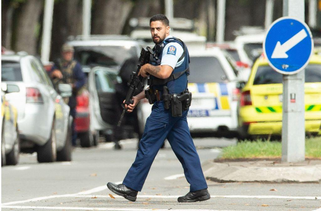 Ein schwer bewaffneter Polizist sichert den Tatort. Foto: SNPA
