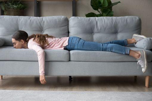 Frau, die zu faul zum Putzen ist, liegt auf Sofa.