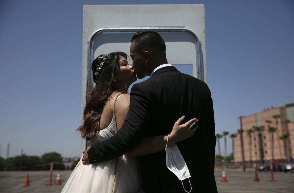 Roselle Querido und Mo de las Alasm küssen sich nach ihrer Trauung. Das Orange County hat Hochzeitskabinen eingerichtet, um Trauungen von Paaren wieder aufzunehmen. Wie  das Coronavirus den Alltag weltweit durcheinanderwirbelt sehen Sie in unserer Bilderstrecke. Foto: dpa/Jae C. Hong