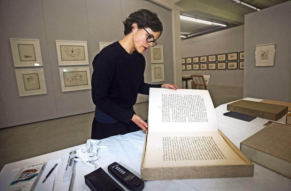 Nicht nur  einzelne Grafiken sind in der Kunsthalle zu sehen, sondern auch eine ganze Reihe Künstlerbücher. Die Kuratorin Melanie Ardjah blättert in einem Exponat. Foto: Ines Rudel