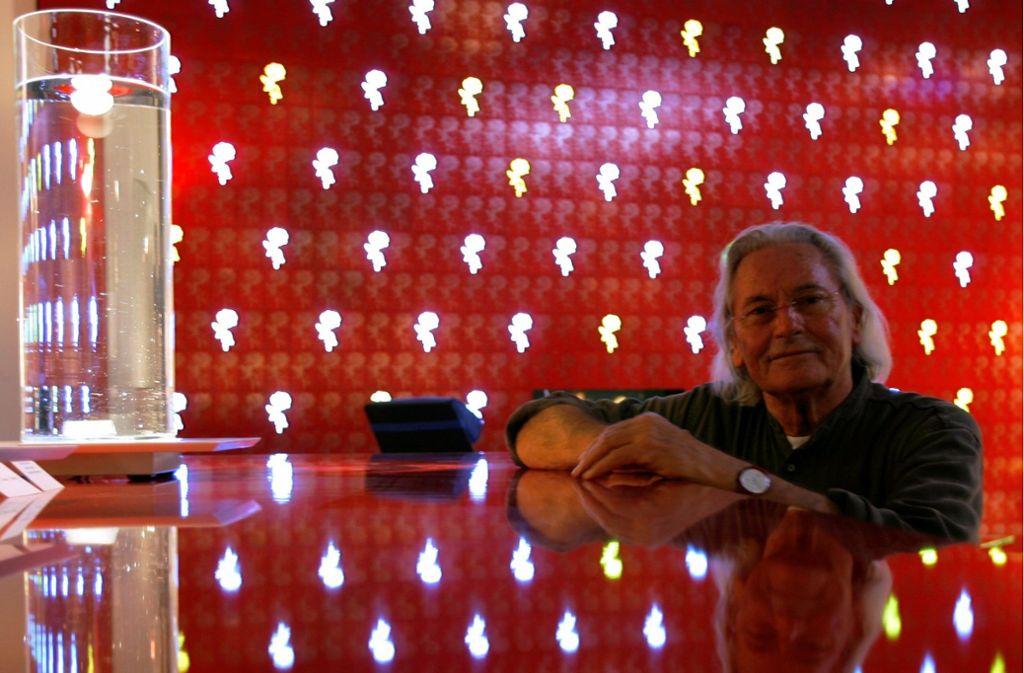 """Ingo Maurer mit seiner Lampe """"Delirium Yum"""" (links) und einer LED-Wand mit Rosenmotiven. Er starb am 21. Oktober im Alter von 87 Jahren. Foto: dpa/Arne Dedert"""