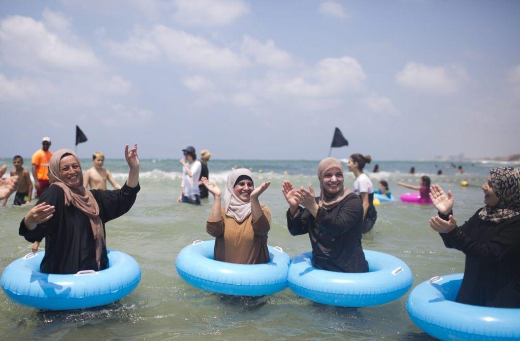 Burkini-Trägerinnen tanzen und singen am Strand von Tel Aviv. Foto: EPA