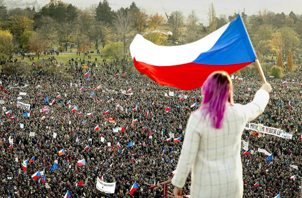 Eine Frau winkt bei einer Großkundgebung gegen die Regierung eine tschechische Flagge von einem Dach – mehr als 250000 Demonstranten fordern Ministerpräsident Babis ultimativ zum Rücktritt auf. Foto: dpa/Petr David Josek