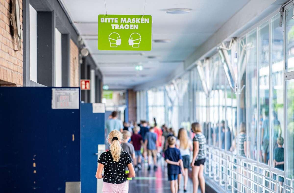 """Auf dem Flur einer Schule hängt ein Schild mit der Aufschrift: """"Bitte Masken tragen"""". Foto: dpa/Guido Kirchner"""