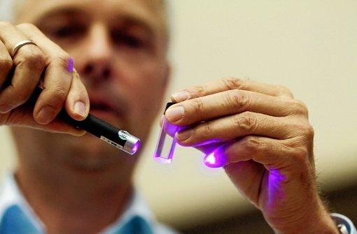 Der Physiker Jörg Wrachtrup von der Uni Stuttgart leuchtet bei der Leser-Uni der Stuttgarter Zeitung mit einem Laserpointer auf einen winzigen Diamanten. Foto: factum/Weise