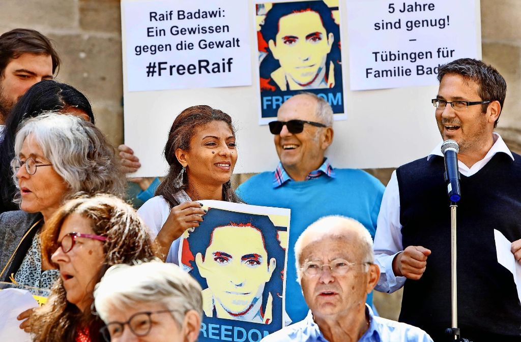 Ensaf Haidar hält ein Foto ihres inhaftierten Mannes Raif Badawi. Die Mahnwachen organisieren  Max Steinacher (rechts vorne) und  Christopher Gohl (ganz rechts). Foto: Haas