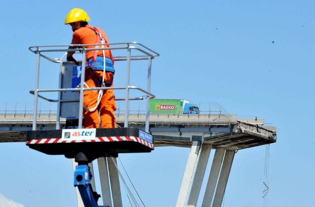 Genua: Ein Arbeiter steht im Korb eines Krans, im Hintergrund ist die eingestürzte Morandi-Autobahnbrücke zu sehen. Foto: dpa