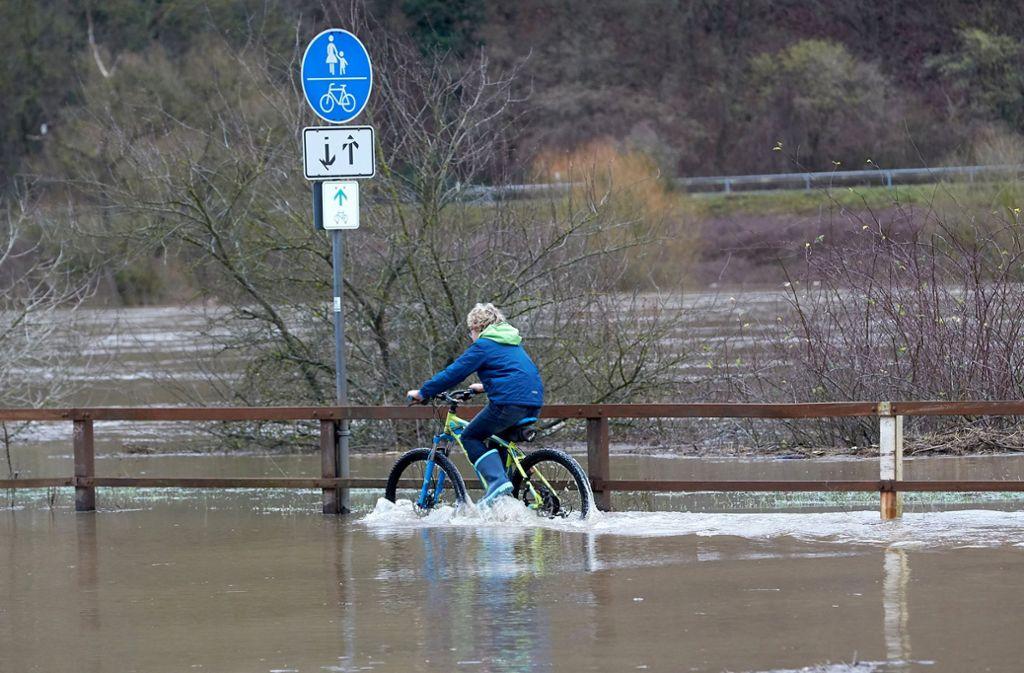 Die Wasserstände steigen. Bei Moselkern in Rheinland-Pfalz scheint das diesen Radfahrer nicht vor einer Spritztour abzuhalten. Foto: dpa