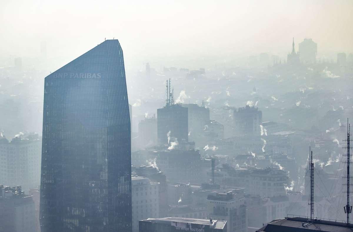 Weißer nebliger Rauch aus Schornsteinen hängt über der Innenstadt von Mailand.  Den höchsten Anteil an Todesfällen in Zusammenhang mit Umweltbelastungen in Europa haben  Bosnien und Herzegowina (27 Prozent). Foto: Claudio Furlan/LaPresse/dpa