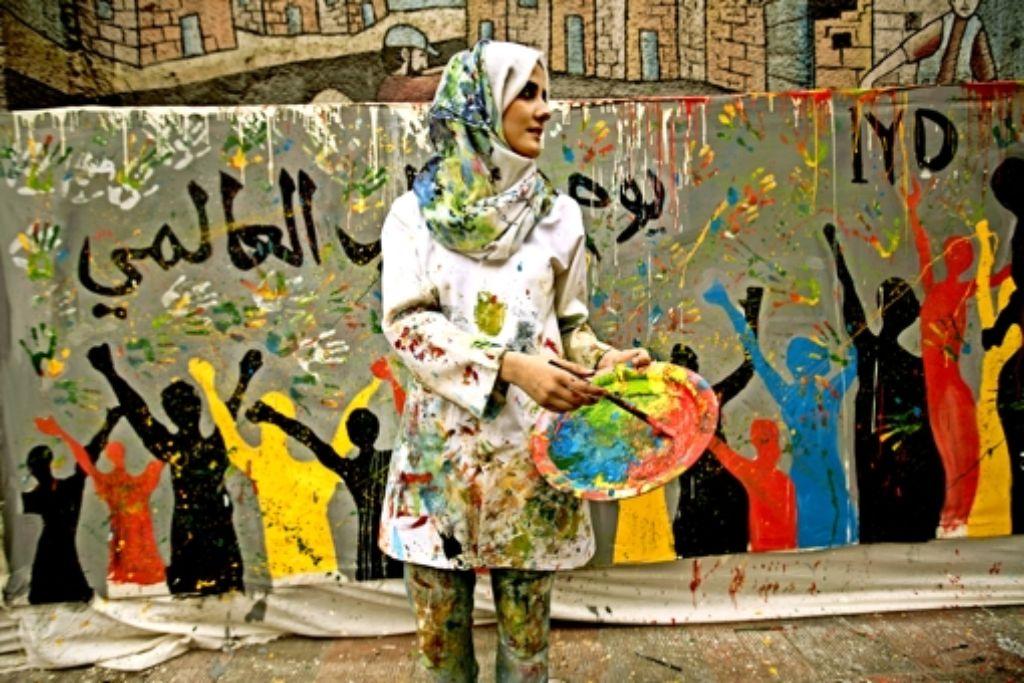 Die Buntheit tut gut: Eine junge palästinensische Künstlerin verschönert eine Mauer in Gaza-Stadt. Foto: AFP