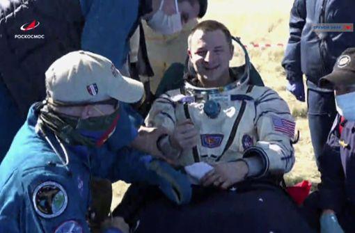 Raumfahrer nach Landung mit Mundschutz und Handschuhen empfangen