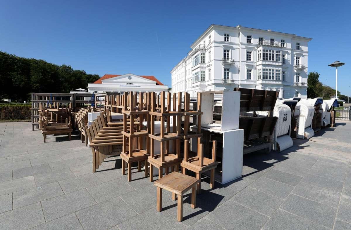 Auf der Uferpromenade vor dem Grand Hotel Heiligendamm stehen Tische und Stühle bereit, die im Außenbereich aufgestellt werden. Das Hotel an der Ostsee, das sich als Gastgeber des G8-Gipfels 2007 einen Namen gemacht hat, hat  am 10. Juni  nach monatelanger Corona-Pause wieder geöffnet . Foto: Bernd Wüstneck/dpa