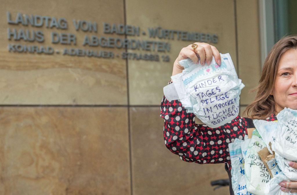 """Auf einer Windel steht der Solgan """"Kindertagespflege in trockene Tücher bringen"""". Foto: dpa"""