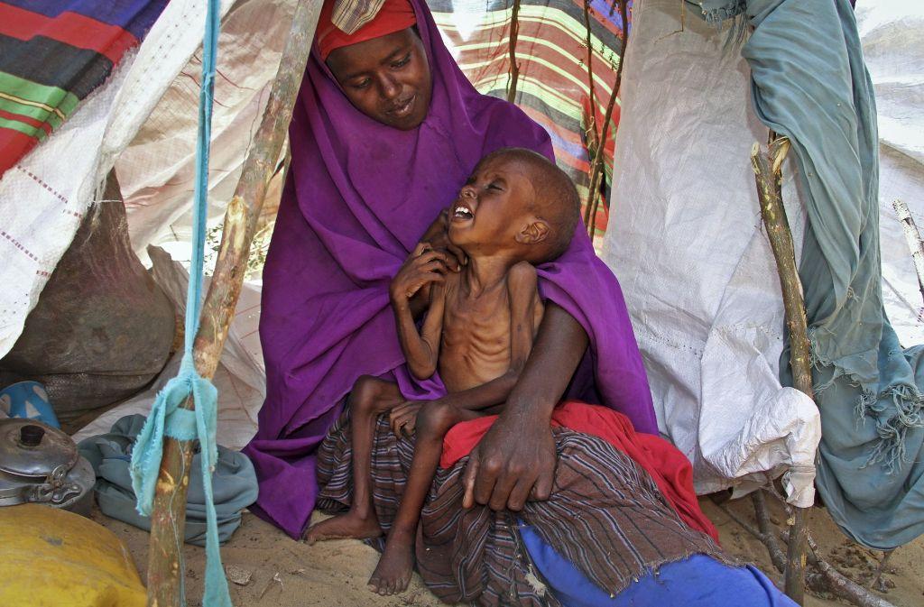 Sahra Muse (32) tröstet ihren unterernährten Sohn Ibrahim Ali (7) in ihrer Unterkunft in einem Lager in Garasbaley am Rande von Mogadischu. Laut UN sind derzeit etwa drei Millionen Menschen von der Dürre in Somalia betroffen. Foto: AP
