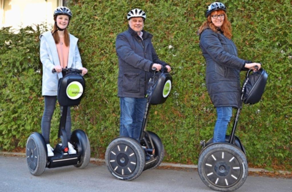 Helmut Butter (Mitte), Conny Willet-Sielaff (r.) und Tochter Alina (l.) sind vom schwebenden Fahrgefühl auf den Segways begeistert. Foto: Fatma Tetik