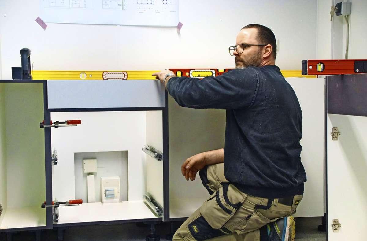 Alles im Lot: Mit der Wasserwaage sorgt der Küchenmonteur im neuen Beutreuungsmodul dafür, dass die Ebenen alle waagrecht sind. Foto: Thomas Krytzner