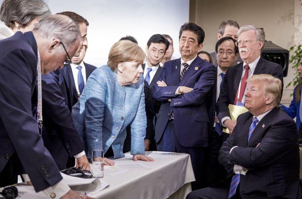 Angela Merkel stützt sich auf den Tisch, Donald Trump verschränkt die Arme. Dieses Bild vom G7-Gipfel in Kanada macht im Internet die Runde. Foto: German Federal Government