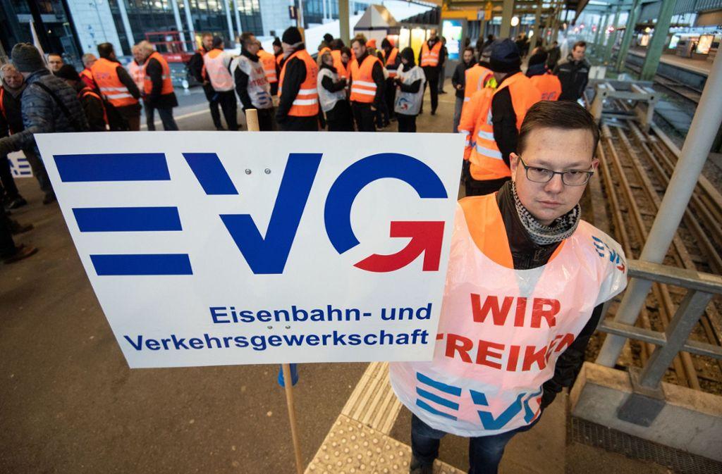 Ein Streikposten hält im Hauptbahnhof ein Plakat der Eisenbahn- und Verkehrsgewerkschaft (EVG). Foto: dpa