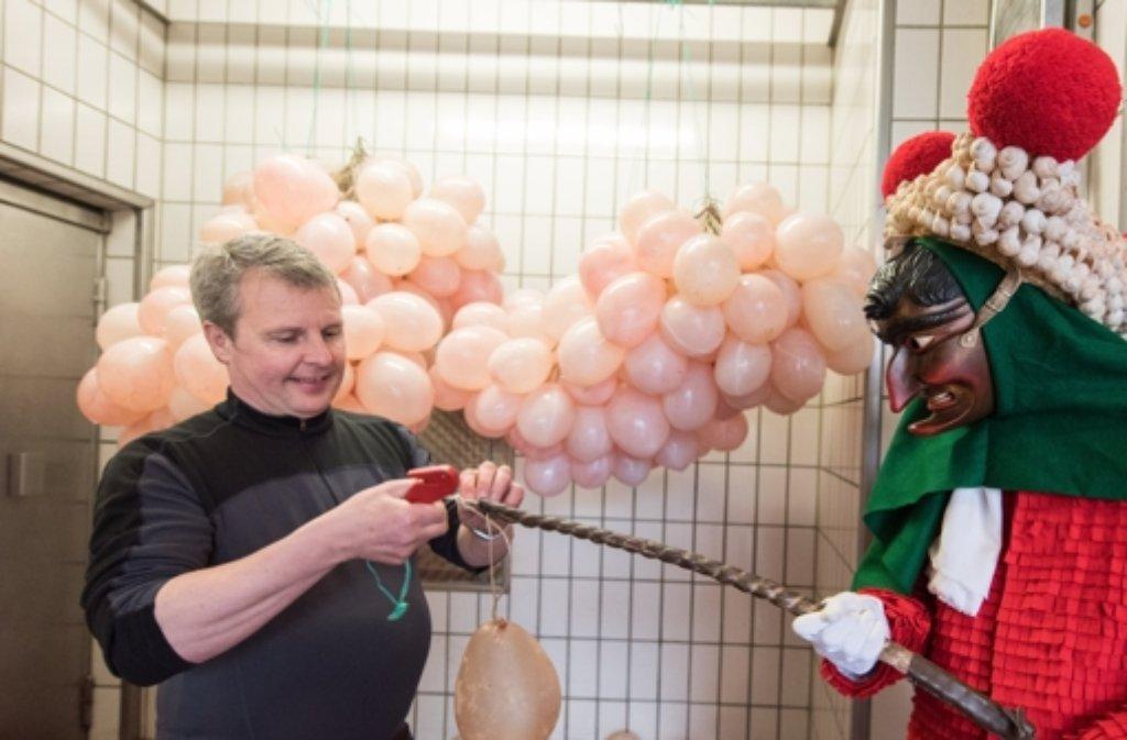 """Metzgermeister Thomas Winterhalter befestigt eine """"Saubloder"""", eine mit Luft gefüllte Schweinsblase, am Hagenschwanz eines Elzacher """"Schuttigs"""". Der Hagenschwanz ist der getrocknete Penis eines Bullen. Foto: dpa"""