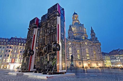 Umstrittenes Kunstwerk: Drei Busse stehen aufrecht vor der Dresdner Frauenkirche Foto: dpa