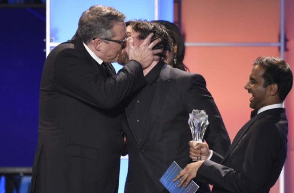 """Adam McKay, links, schmatzt Christian Bale bei dessen Triumph in der Kategorie """"Beste Komödie""""  für """"The Big Short"""".  Aziz Ansari, der die Auszeichnung überreicht, freut's. Foto: dpa"""